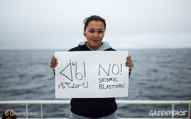 greenpeace-clara-natanine-on-the-ddeck-of-the-arctic-sunrise-with-an-anti-seismic-blasting-sign-that-she-made-herself